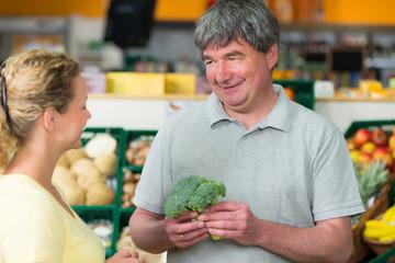 verkäufer berät kundin beim gemüse