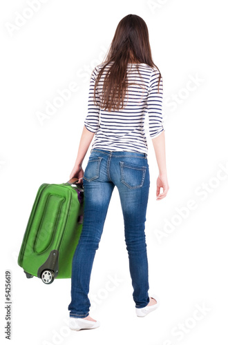 back view of walking  woman  with suitcase.