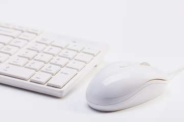 Close up of white wireless keyboard  and wired mouse
