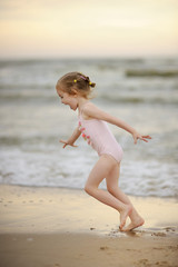 Little girl playing on a beach