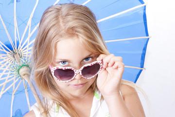 niña con sombrilla y gafas de sol sonriendo