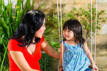Asian Mother and daughter at home in garden