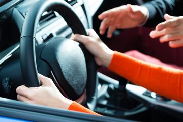 Frau in einem Fahrschule Auto macht Führerschein