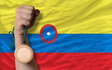 Bronze medal for sport and  national flag of columbia