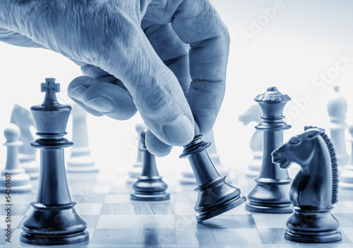 Hand moving a chess piece on board - 54261407