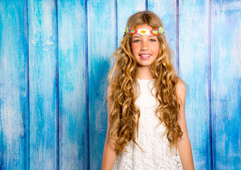 Blond happy hippie children girl smiling on blue wood