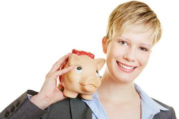 Lächelnde Frau mit Sparschwein auf Schulter