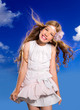 Blond girl with fashion dress blowing hair in blue sky