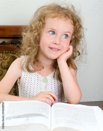 Cute little smiling girl reading a book