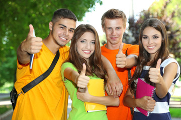 Happy group of young students standing in park