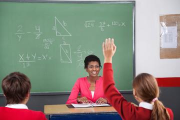 Teenage Girl Raising Hand While Teacher Looking At Her