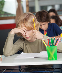 Bored Schoolboy Sitting At Desk In Classroom