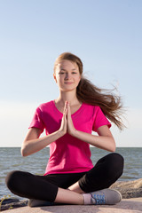 Girl in lotus pose sitting near sea
