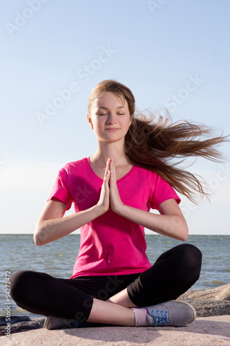 Girl in lotus pose sitting near sea
