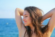 Quadro Beautiful woman relaxing with closed eyes on blue sea background