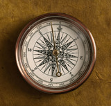 Old compass on brown backgound
