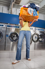 Woman Carrying Basket Of Dirty Clothes In Laundry