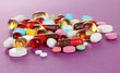 Assortment of pills, tablets and capsules on purple background