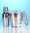 Metal ice bucket and shaker on blue background
