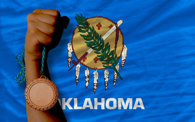 Bronze medal for sport and  flag of american state of oklahoma