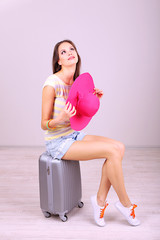 Beautiful girl with suitcase in room