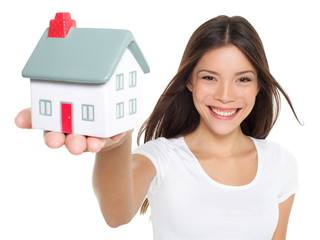 Home / house concept - woman holding mini house