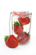 strawberries in a glass jar with a bow