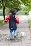 Small boy jumping in a puddle  in a park