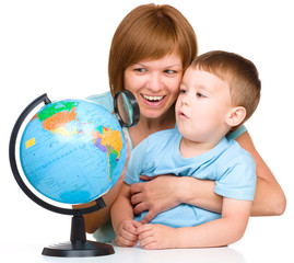 Mother is looking at globe with her son