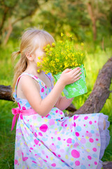 Little girl sitting on a branch of a tree and smelling the flowe