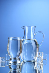 Glass pitcher of water and glass on blue background