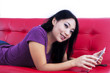 Attractive female lying on sofa with e-tablet - isolated