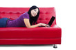 Beautiful female lying on red sofa - isolated