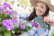 Cheery Young Adult Woman Wearing Hat Gardening Outdoors