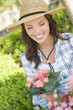 Cheerful Young Adult Woman Wearing Hat Gardening Outdoors
