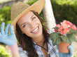 Pretty Young Adult Woman Wearing Hat Gardening Outdoors