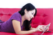 Beautiful female using touchpad on red sofa -isolated