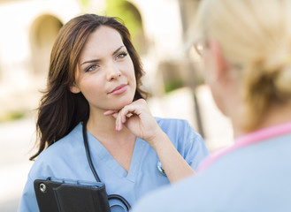 Two Attractive Female Doctors or Nurses Talking Outside
