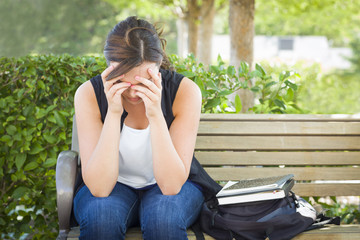 Depressed Young Woman Sitting Alone on Bench Next to Books