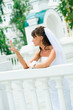 pensive bride in a white dress looks at manicure