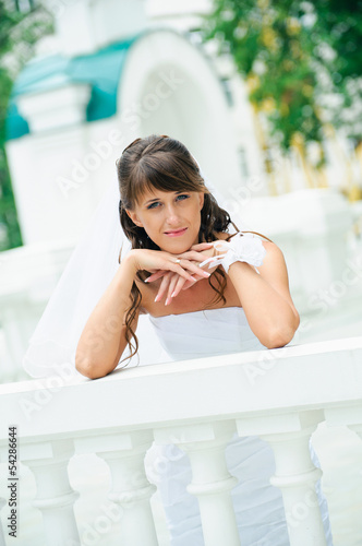 pensive bride in white dress has leant elbows on handrail