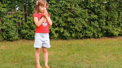 девочка ест яблоко на улице, лето, зелёная трава