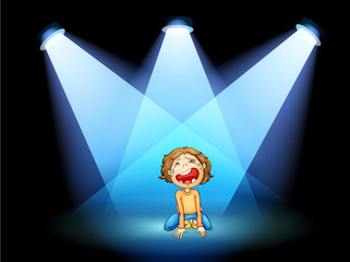 A girl crying in the middle of the stage with spotlights