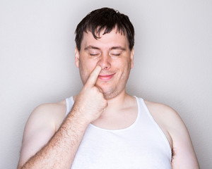 Man picking his nose with a white shirt on
