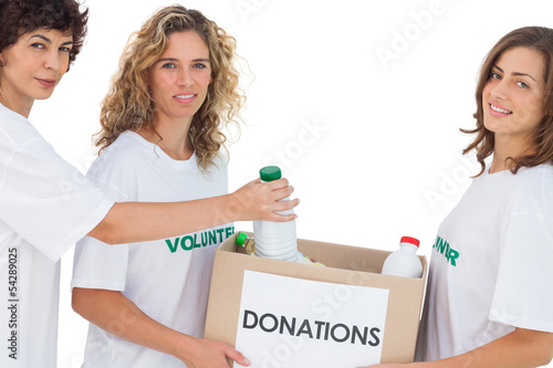 Volunteer women putting food in donation box