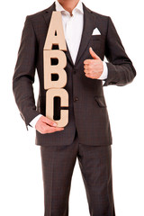 Handsome young man in classic suit and with letters abc