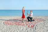 Loving couple on sea beach - a man making proposal to his woman