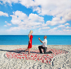 man making proposal to his woman in the heart of roses petals on