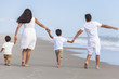 Mother, Father & Two Boy Children Family Walking on Beach