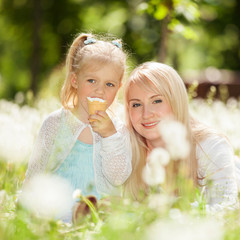 Mother and daughter eating ice-cream in the park